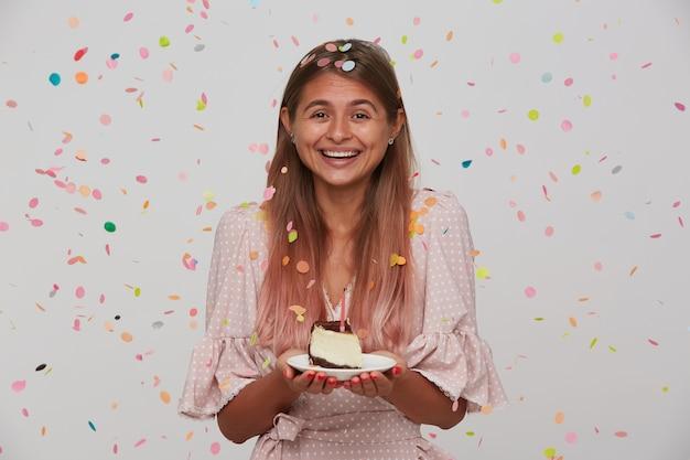 Счастливая молодая красивая длинноволосая женщина показывает свои приятные эмоции во время празднования дня рождения, позитивно улыбаясь с тортом в поднятых руках, позирует над белой стеной