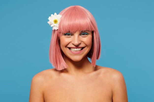 Happy young beautiful pink haired woman with bob haircut looking cheerfully at camera with wide charming smile, standing over blue background with white flower in her hair