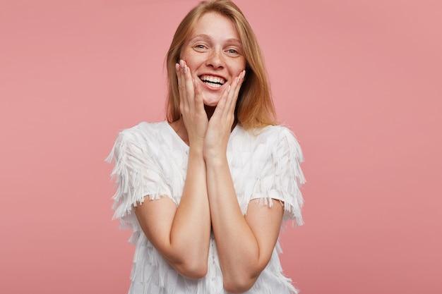 Счастливая молодая красивая рыжая женщина, одетая в элегантную одежду, держа поднятые ладони на щеках, весело глядя в камеру, изолированные на розовом фоне