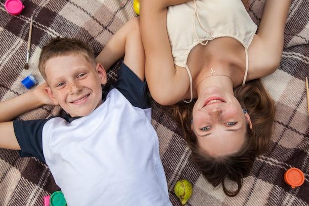 얼굴에 주근깨가 있는 행복한 젊고 아름다운 자매와 형제는 격자 무늬에 누워 웃으면서 이빨 미소로 카메라를 바라보고 있습니다.