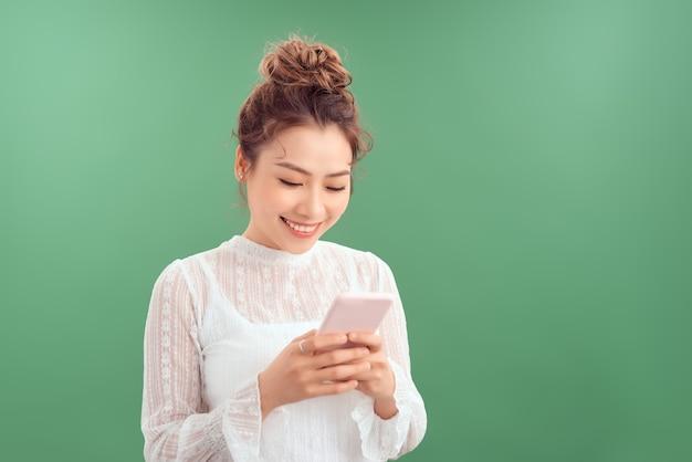 Счастливый молодой красивый набор текста на мобильном телефоне, стоя изолированным на зеленом фоне.