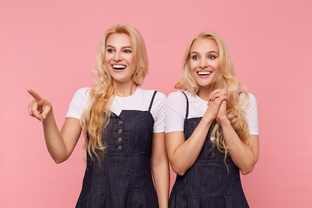 ピンクの背景の上に立って、元気に笑っている間、完璧な白い歯を見せて長い緩い髪の幸せな若い美しい白い頭の女性