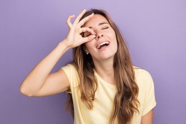 Felice giovane bella donna in maglietta beige che fa segno ok guardando attraverso questo segno