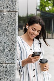 야외에서 야외에서 포즈를 취한 행복한 젊은 여성 사업가가 이어폰으로 음악을 들으며 커피를 마시는 휴대폰으로 채팅을 하고 있습니다.