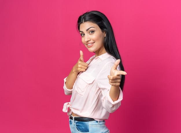Felice giovane bella donna in abiti casual sorridenti fiduciosi che puntano con le dita davanti