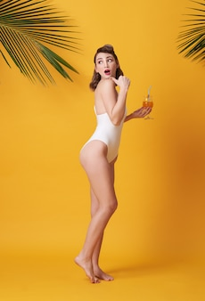 Happy young beautiful woman dressed in swimwear holding a orange