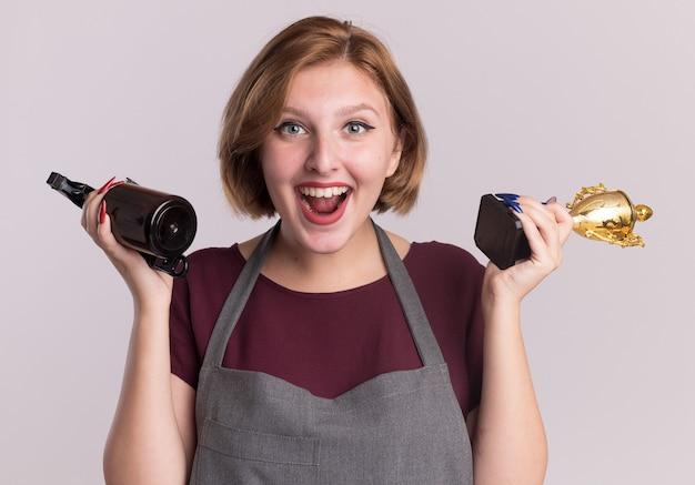 Felice giovane bella donna parrucchiere in grembiule azienda trofeo d'oro e flacone spray con trimmer guardando davanti sorridente in piedi sopra il muro bianco