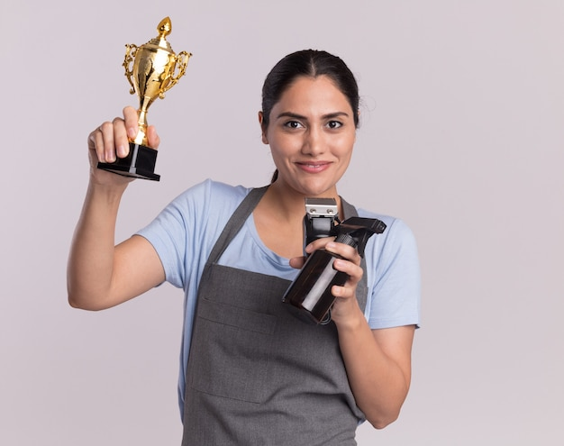 Parrucchiere di giovane bella donna felice in grembiule che tiene macchina trimmer trofeo d'oro con flacone spray guardando la parte anteriore con il sorriso sul viso in piedi sopra il muro bianco