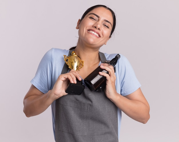 Felice giovane bella donna parrucchiere in grembiule azienda trofeo d'oro trimmer macchina con flacone spray sorridente con gli occhi chiusi in piedi sopra il muro bianco