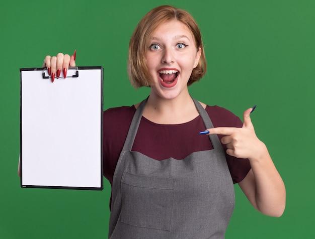 녹색 벽 위에 유쾌하게 서있는 그것에 검지 손가락으로 가리키는 빈 페이지 클립 보드를 들고 앞치마에 행복 한 젊은 아름 다운 여자 미용사