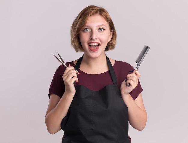 Счастливая молодая красивая женщина-парикмахер в фартуке, держащая расческу для волос и ножницы, глядя на переднюю улыбку, стоя над белой стеной
