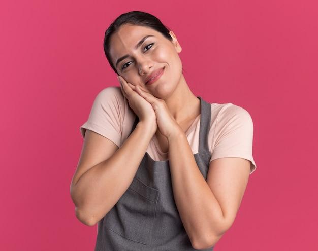 ピンクの壁の上に立って感謝の気持ちを笑顔で一緒に手のひらを保持しているエプロンで幸せな若い美しい女性の美容師