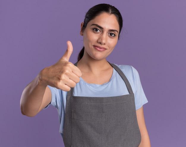 紫色の壁の上に立って親指を見せて笑顔の正面を見てエプロンで幸せな若い美しい女性の美容師