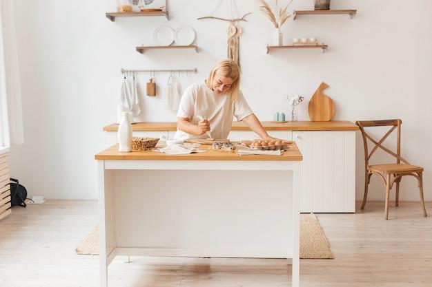 Счастливая молодая красивая женщина-домохозяйка-пекарь раскатывает тесто на кухонном столе
