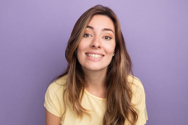 Счастливая молодая красивая женщина в бежевой футболке, глядя в камеру, широко улыбаясь, стоя на фиолетовом фоне