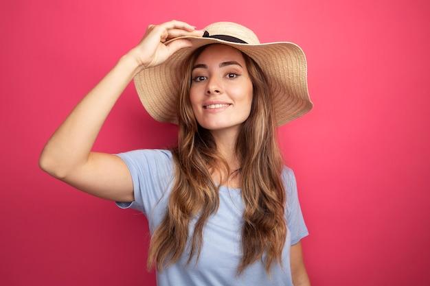 Счастливая молодая красивая женщина в голубой футболке и летней шляпе, глядя в камеру, весело улыбаясь, стоя на розовом фоне