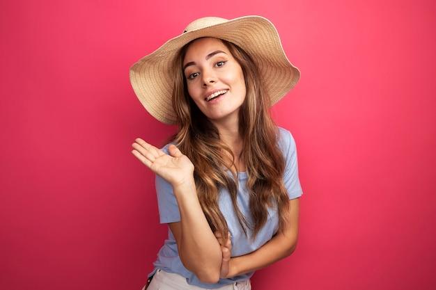 Счастливая молодая красивая женщина в синей футболке и летней шляпе, глядя в камеру, улыбаясь машет рукой