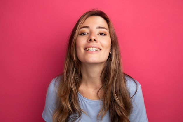 핑크 위에 서있는 얼굴에 미소로 카메라를보고 파란색 티셔츠에 행복 한 젊은 아름 다운 여자