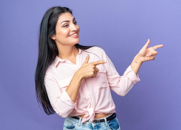 Счастливая молодая красивая женщина в повседневной одежде удивлена, указывая указательными пальцами в сторону, стоящую над синей стеной