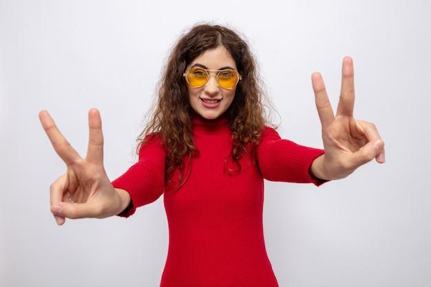 黄色いメガネをかけて元気に笑顔の赤いタートルネックの幸せな若い美しい女性は、白の上に立っているvサインを示しています