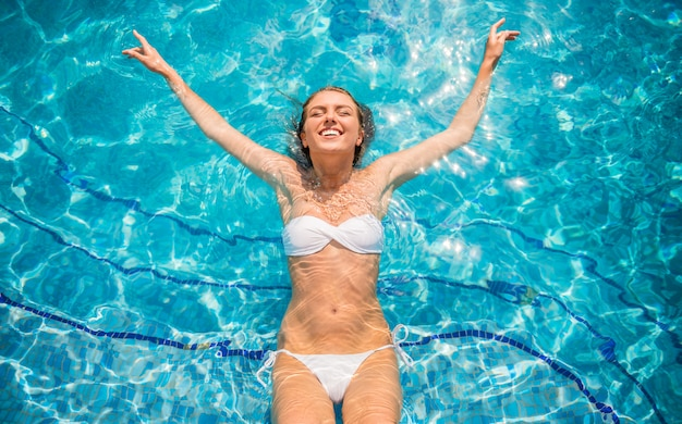 Happy young beautiful woman is relaxing in swimming pool.