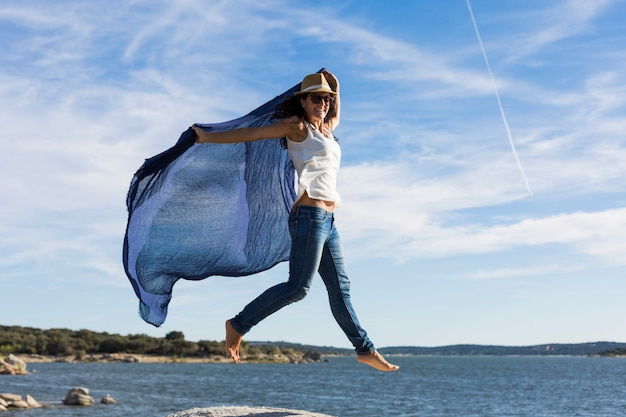 Happy young beautiful woman playing with a blue shawl at the beach. fun, wind and lifestyle