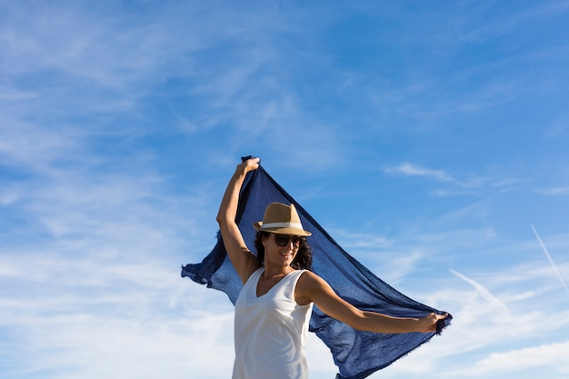 Happy young beautiful woman playing with a blue shawl. fun, wind and lifestyle. blue sky background