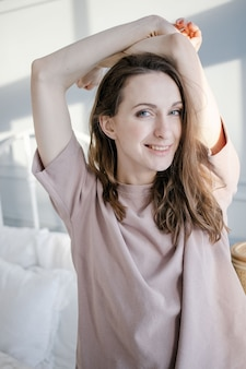 Happy young beautiful woman pulls her hands up, standing next to the bed in her bedroom at home
