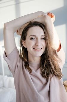 Счастливая молодая красивая женщина поднимает руки вверх, стоя рядом с кроватью в своей спальне дома. люди и утренняя концепция.