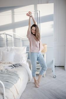 幸せな若い美しい女性は、自宅の寝室のベッドの横に立って、手を引き上げます