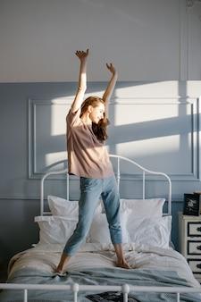 Счастливая молодая красивая женщина поднимает руки вверх, стоя на кровати в своей спальне у себя дома.