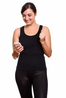 Happy young beautiful woman using phone and getting good news