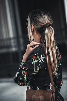 花柄のドレスを着て街の通りスタイリッシュなファッションモデルで歩いて幸せな若い美しい女性