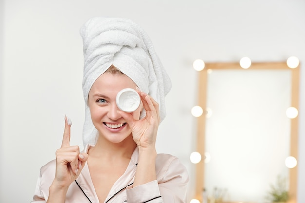 Happy young beautiful woman with white towel on head showing her facial moisturizer while holding it by left eye