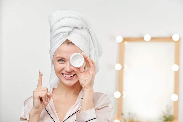 Счастливая молодая красивая женщина с белым полотенцем на голове показывает увлажняющий крем для лица, держа его левым глазом