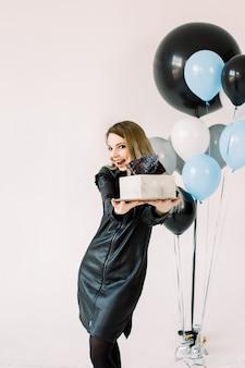 黒革のドレスで幸せな若い誕生日の女の子、笑みを浮かべて、白い背景の上に立って、白い正方形のケーキを保持しています。大きな気球、背景色は青、白、黒