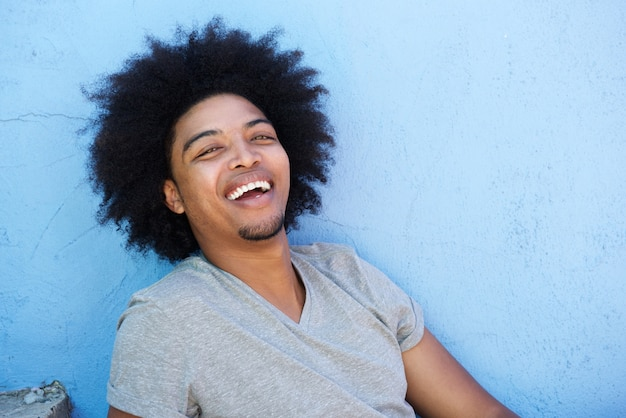 Happy young black man with afro laughing