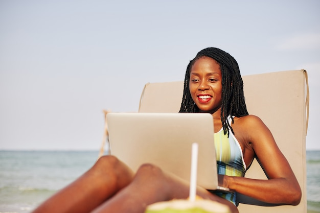 Happy young black woman on chaise-lounge