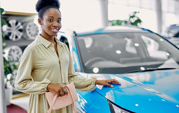 Happy young black woman in dealership