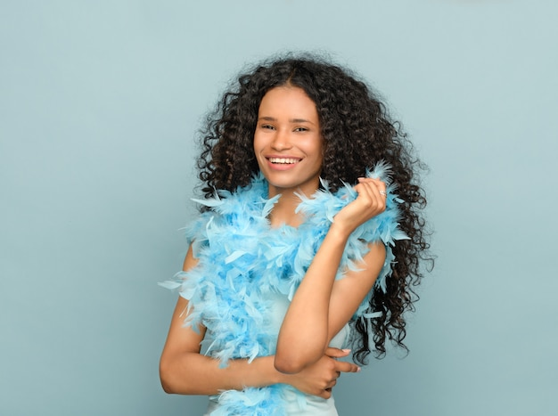 Happy young black woman in a fashion portrait on blue