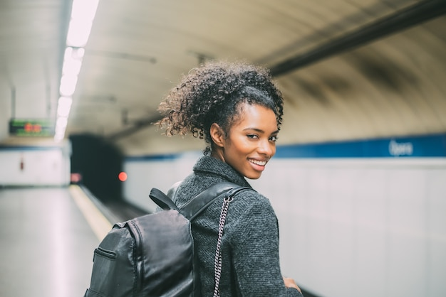 Happy young black woman inside the underground station waiting for the train