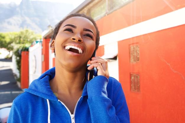 屋外の携帯電話で笑う幸せな若い黒人の女性