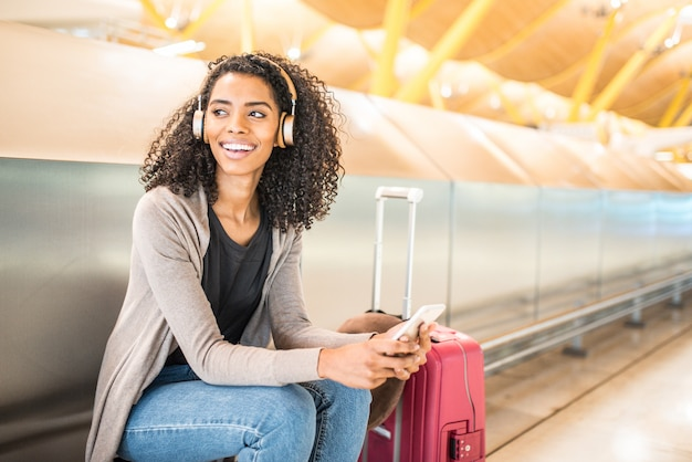 Happy young black woman listening music with headphones and mobile phone at the airport