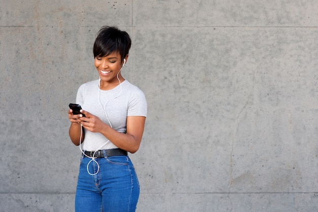 Happy young black woman looking at mobile phone and listening to music