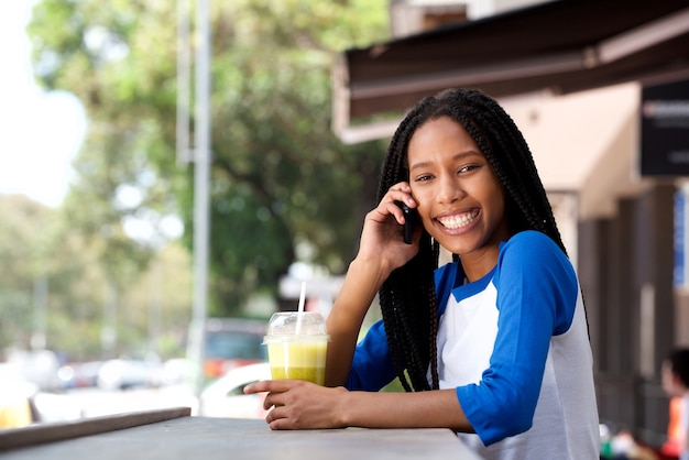 Happy young black woman talking cell phone at cafe outdoors