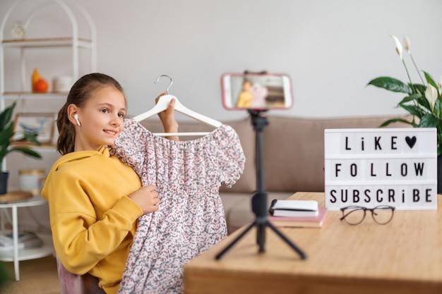 추종자와 패션 의류에 대한 그녀의 의견을 공유하는 행복 한 젊은 블로거 소녀