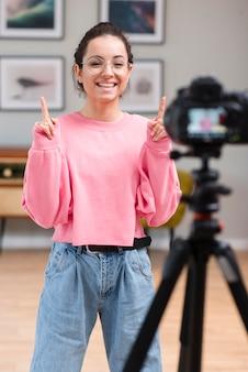 Счастливый молодой блоггер, улыбаясь в профессиональную камеру