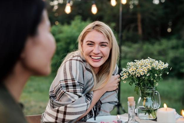 自然環境での夕食の会話中に提供されたテーブルで彼女の友人を見て歯を見せる笑顔で幸せな若いブロンドの女性
