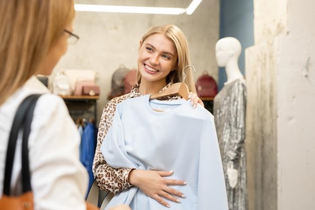 衣料品部門で新しい白いスウェットシャツを試しながら彼女の友人を見て歯を見せる笑顔で幸せな若いブロンドの女性