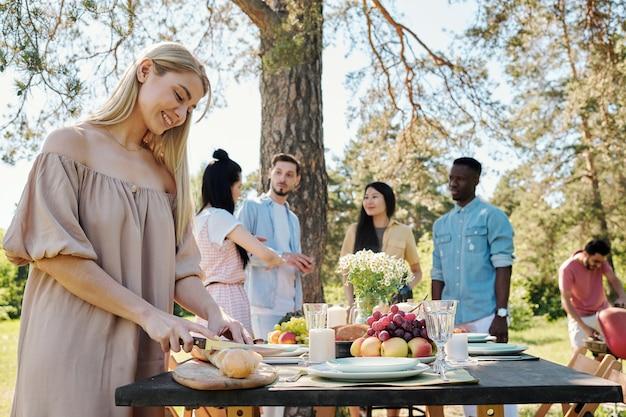 저녁 식사를 위해 제공되는 테이블에 의해 나무 보드에 신선한 바게트를 절단 행복 젊은 금발 여자